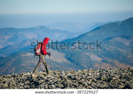 Male sportsman tourist walking on the rocky mountain ridge with beautiful mountains on background. Man is wearing red jacket and has trekking sticks and backpack on. Sunny autumn day. - stock photo