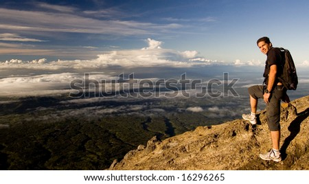Male standing on top of mountain with fulfilled expression - stock photo
