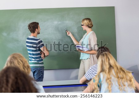 Male student and teacher pointing at blackboard in the class - stock photo