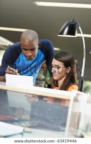 male student helping her mate with homeworks in library. Vertical shape, front view, waist up, copy space - stock photo