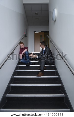 Male student is sitting on the stairs in his school, with his teacher next to him. He is telling him off for his behaviour. - stock photo