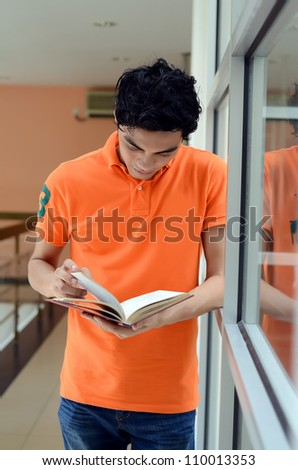 male student reading notes at the university - stock photo