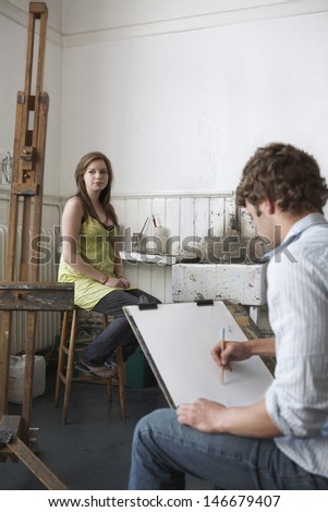 Male student sketching female model in art class - stock photo
