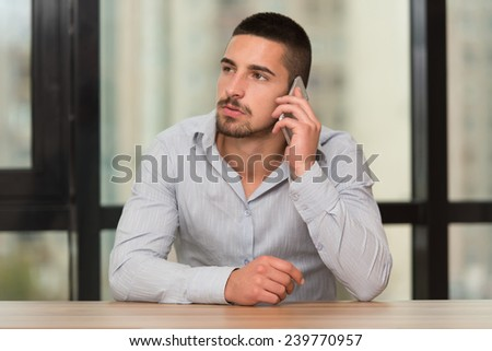 Male Student Talking On The Phone In Library - Shallow Depth Of Field - stock photo