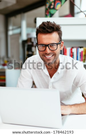Male student with geek glasses in front of his laptop - stock photo