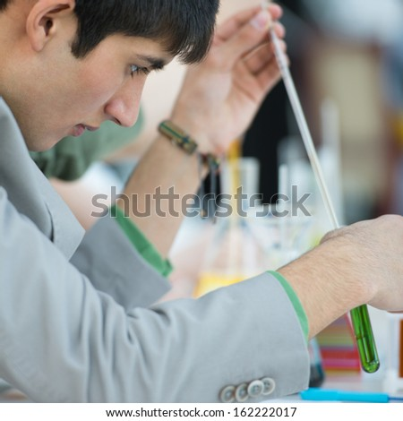 Male student with group of classmates on background working at the school or college or university laboratory during chemical lesson - stock photo