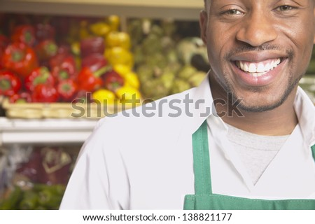 Male supermarket worker smiling - stock photo