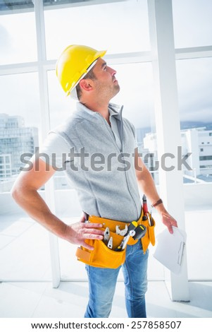 Male supervisor with clipboard inspecting building - stock photo