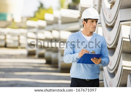 Male supervisor with clipboard inspecting stock at site - stock photo