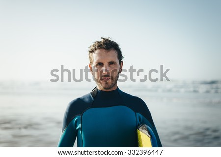 Male surfer beach lifestyle portrait. Man in wetsuit with bodyboard surfing equipment. - stock photo