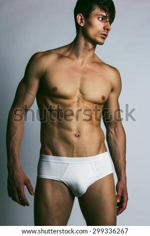 Male swimwear & underwear concept. Handsome muscular male model in trendy white underwear posing over grey background. Studio shot - stock photo