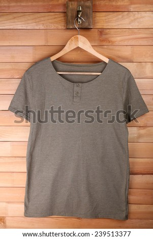 Male t-shirt on hanger on wooden wall background - stock photo