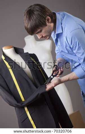 male tailor working on business jacket with scissors - stock photo