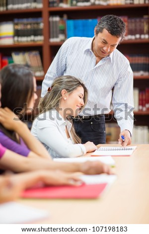 Male teacher explaining something to his students - stock photo