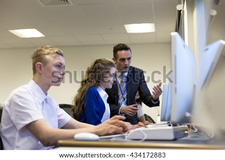 Male teacher helping one of his students who is working on a computer. - stock photo