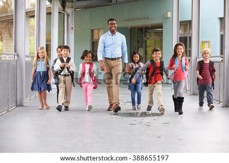 Male teacher walking in corridor with elementary school kids - stock photo