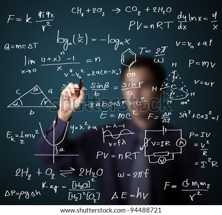 male teacher writing various high school maths and science formula on whiteboard - stock photo