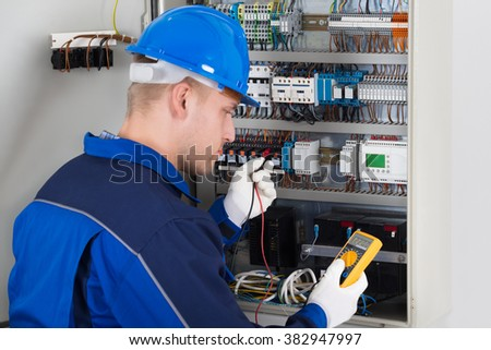 Male Technician Examining Fusebox With Digital Insulation Resistance Tester - stock photo