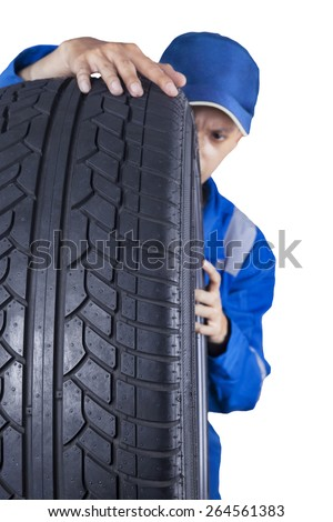 Male technician expert checking a tire texture while wearing a blue uniform, isolated on white - stock photo