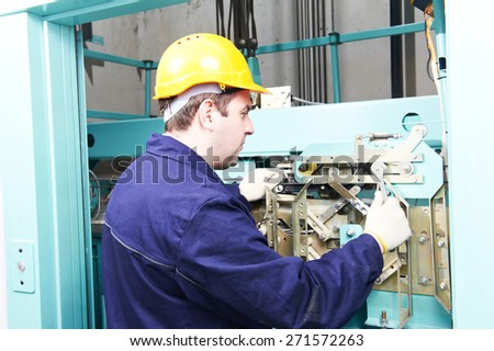 Male technician machinist worker at work adjusting elevator mechanism of lift with spanner - stock photo