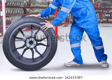 Male technician with a blue clothes changing a tire in the workshop - stock photo
