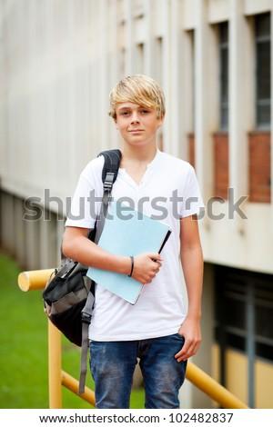 male teen high school student in front of school building - stock photo