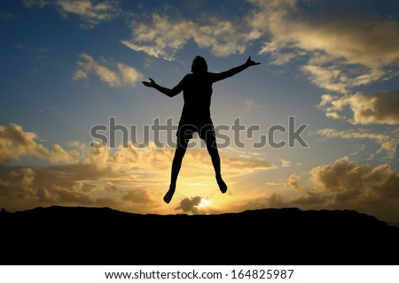 male teen jumping in sunset  - stock photo