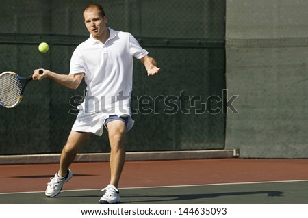 Male tennis player swinging tennis racket in forehand motion on tennis court - stock photo