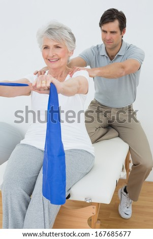 Male therapist assisting senior woman with exercises in the medical office - stock photo