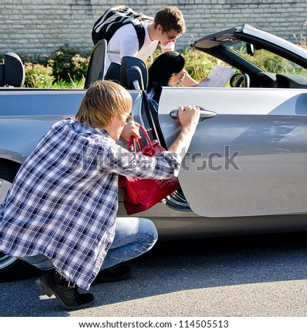 Male thief stealing handbag from the car while his accomplice distracts female driver - stock photo