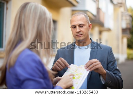 Male tourist asks for directions from a woman - stock photo