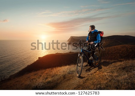 male tourist with headphones and a tablet on a bicycle stopped water at a very beautiful night scenery - stock photo