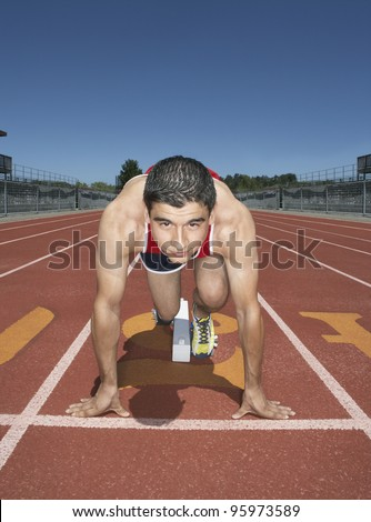 Male track athlete at the starting line - stock photo