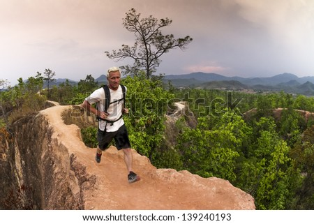 Male trail runner with white shirt and backpack running narrow path in red canyon - stock photo