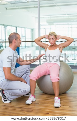 Male trainer assisting woman with abdominal crunches at the gym - stock photo