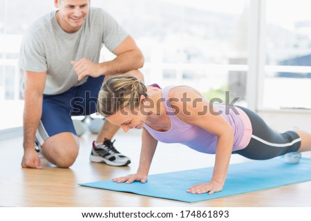 Male trainer assisting woman with push ups in fitness studio - stock photo