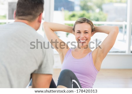 Male trainer helping woman doing sit ups in fitness club - stock photo