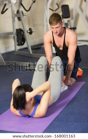 Male trainer helping young woman do abdominal crunches at a gym - stock photo