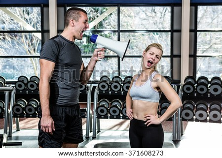 Male trainer motivating fit woman with megaphone at gym - stock photo