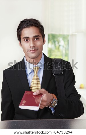 Male traveler shows passport at counter - stock photo
