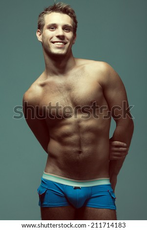 Male underwear fashion concept. Emotive portrait of young man in blue briefs posing with hands behind muscular body over blue background. White shiny smile. Vogue style. Studio shot - stock photo