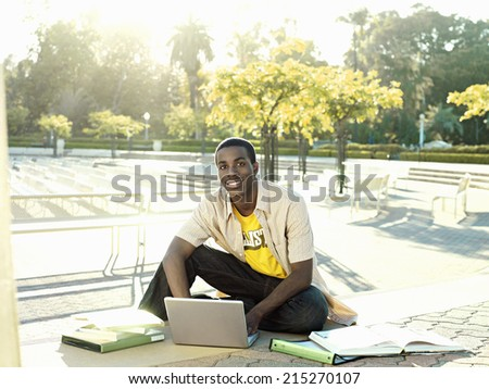 Male university student sitting on ground with textbooks, using laptop, smiling, portrait - stock photo