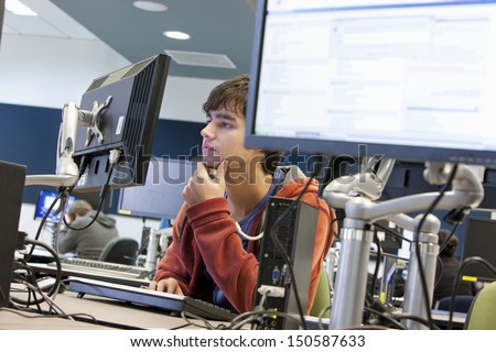 Male university student using computer in college - stock photo