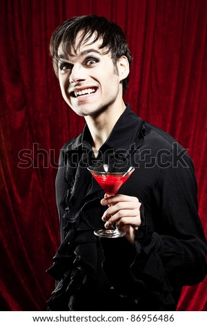 Male vampire is offering a bloody halloween drink - stock photo