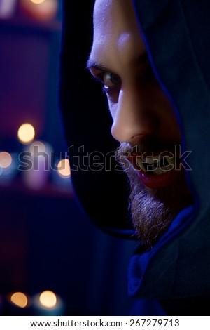 Male vampire opening mouth with fangs - stock photo
