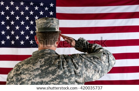 Male Veteran soldier, back to camera, saluting United States of America flag.  - stock photo