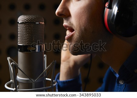 Male Vocalist Singing Into Microphone In Recording Studio - stock photo