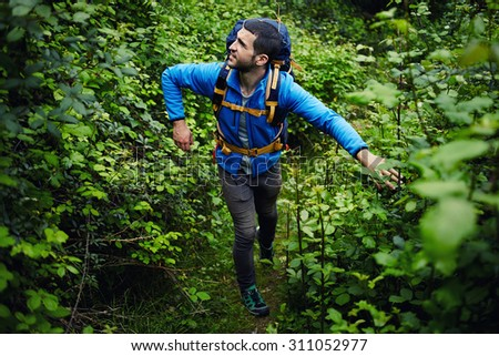 Male wanderer walking through the woods overcoming plants obstacles while hiking in the forest, portrait of a young attractive tourist with backpack walking in green jungle during adventure vacation - stock photo