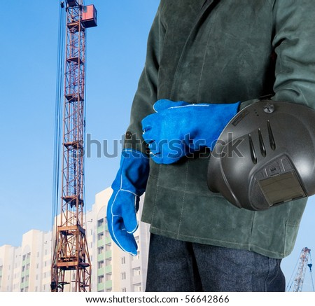 male welder closeup with welding equipment on building background - stock photo