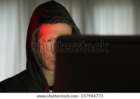 Male with criminal intentions at a computer on the internet. - stock photo